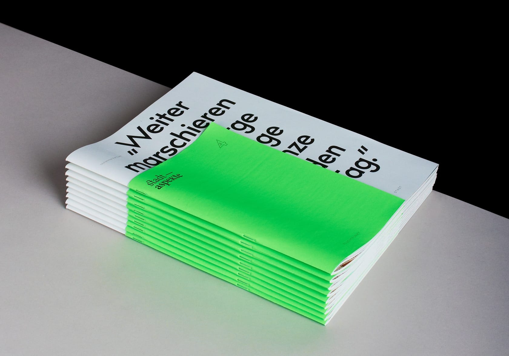A stack of nine magazines of the 4th issue of Stadaspekte in front of a grey and black background